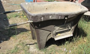 This wheelbarrow has an adjustable slide that opens for feeding grain along a fenceline feeder.