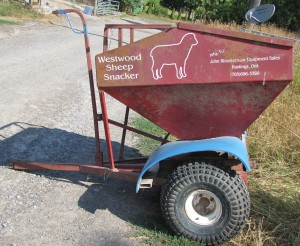 The Sheep Snacker is manufactured locally and is pulled behind an ATV to feed grain in the field. A rotating drum on the axle has openings which result in grain being fed in piles rather than a line, reducing trampling and waste.